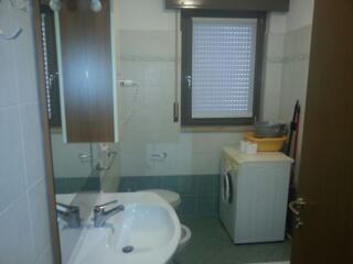 Il bagno con doccia e lavatrice di uno dei bilocali del Teodolinda